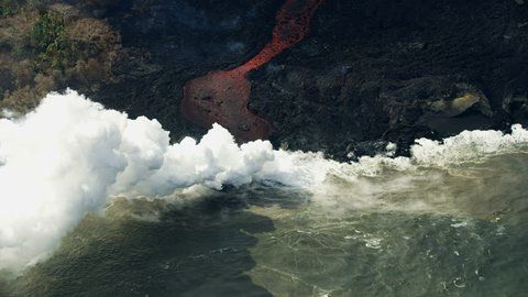 Aerial river of moving red hot liquid magma pouring into Pacific ocean lava rock cooling and solidifying toxic steam rising Hawaii USA RED WEAPON