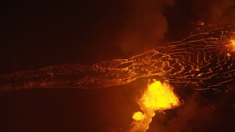 Aerial golden hot liquid lava from open fissures pouring towards Pacific ocean lava rock cooling and solidifying toxic steam rising Kilauea Hawaii USA RED WEAPON