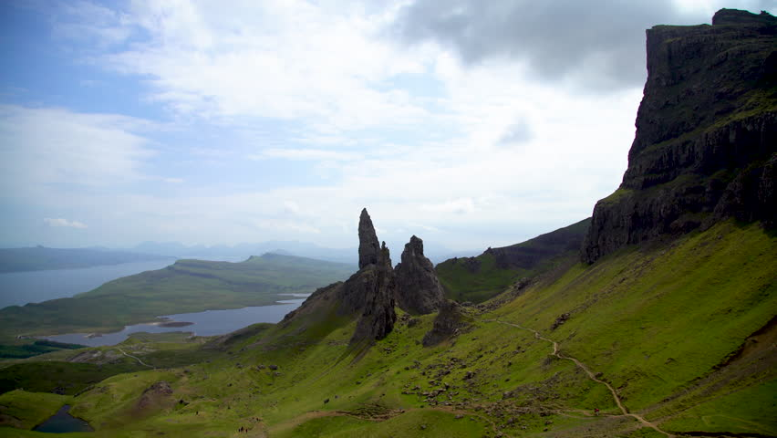 Travellers viewpoint Scotlands Old Man of Storr rock pinnacles on the Isle of Skye landscape view over the Sound of Raasay UK  | Shutterstock HD Video #1018453207