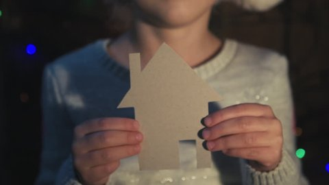 Happy child in Santa hat holding paper house, dreaming of new home.