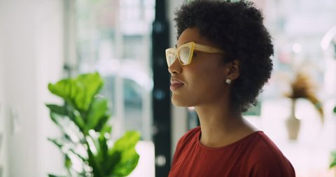 Stylish black woman taking pair of yellow sunglasses and trying them on in interior boutique clothing store with soft day lighting. Close up shot on 4k RED camera.