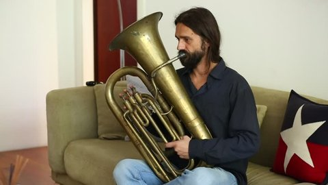 Stock footage of joyful Caucasian man with long hair and beard playing old weary tin tuba in home interior, sitting on sofa, making funny faces.