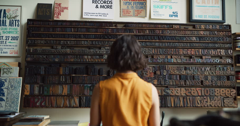 Thoughtful female artist looking at a wall of letters for printmaking in interior creative studio with soft day lighting. Medium shot on 4k RED camera.