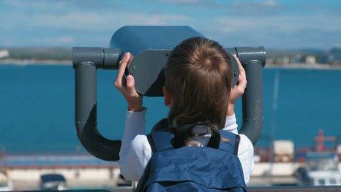 Unrecognizable boy looks through binoculars at the sea.