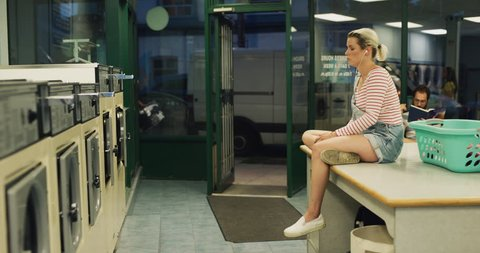 Young woman sitting on a laundry machine and saying hello to a friend in interior small laundromat with bright interior lighting. Wide to Medium shot on 4k RED camera.
