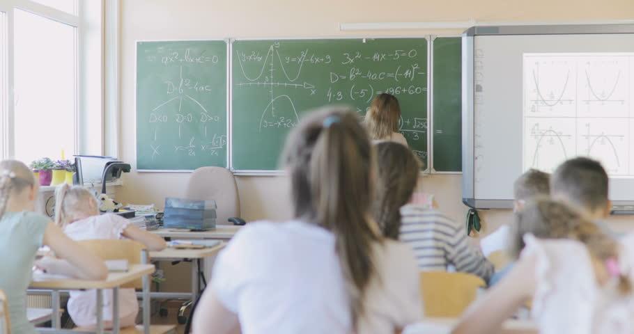 School Teacher Writes Examples in Mathematics on the Chalkboard. Schoolchildren Pull Hands Up | Shutterstock HD Video #1018662367
