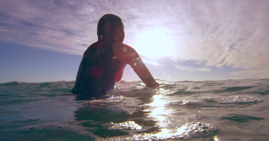 Young female surfer sitting on surboard and contemplating her swim in the ocean in Australian beach with bright day lighting. Medium shot on 4k RED camera. | Shutterstock HD Video #1018684027
