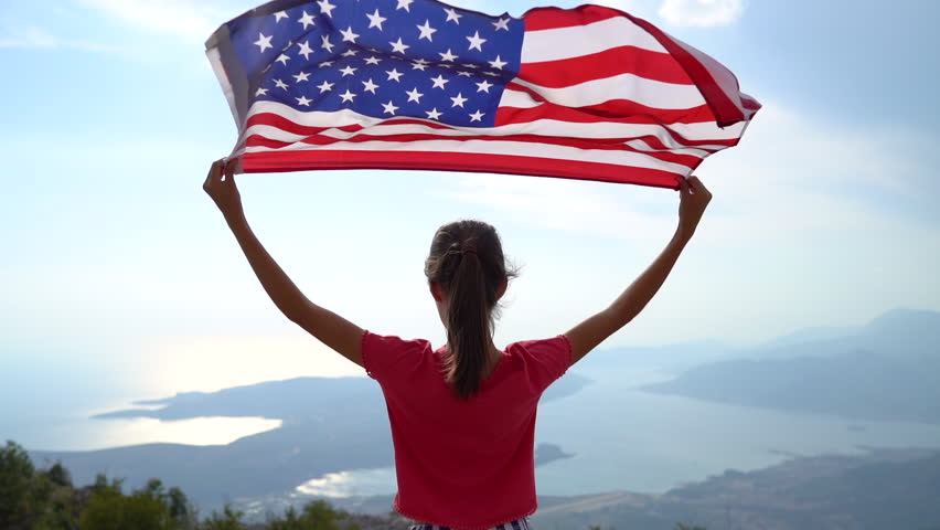 Child girl is waving American flag on top of mountain at sky background. Footage in slow motion | Shutterstock HD Video #1018698997