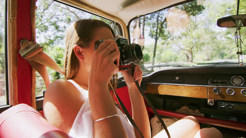 Enthusiastic woman photographs man as young couple drive a vintage car along a road in the country, natural daytime sunlight in Australia. Shot from the backseat, medium shot on 4K RED camera.