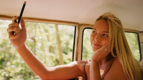 Beautiful blonde woman looks at her phone and takes selfies in backseat of a vintage car as it drives through the country in the summer, in Australia in bright daylight. Medium shot on 4K RED camera