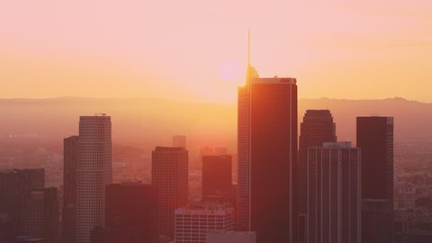 Aerial view of colorful sunset behind tall buildings and skyscrapers of downtown Los Angeles, California, with bright sunset lighting. Wide shot on 4k RED camera