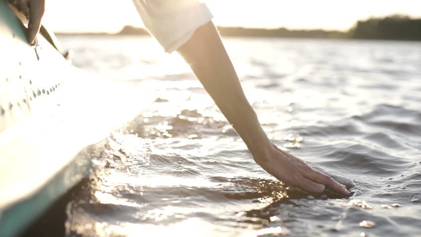 At sunset, close-up the hand of a girl moving through the water | Shutterstock HD Video #1018788877