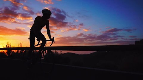 Silhouette of a man riding a Bicycle at sunset on a mountain road side view. Slow motion steadicam