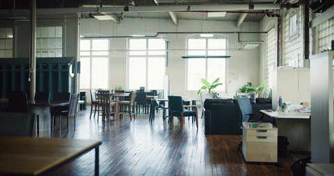 Upscale modern renovated empty industrial office with wood floors brick walls and high ceilings during the daytime. Wide and long shot on 4K RED footage on a gimbal tracking backwards.