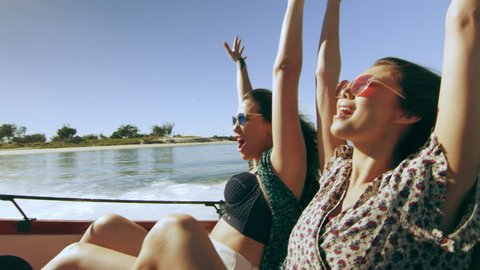 Boat trails in the water and two beautiful young women having fun in a wooden motorboat, putting their hands up, laughing, wind in their hair. Medium to long shot on 4K RED camera with lens flare.