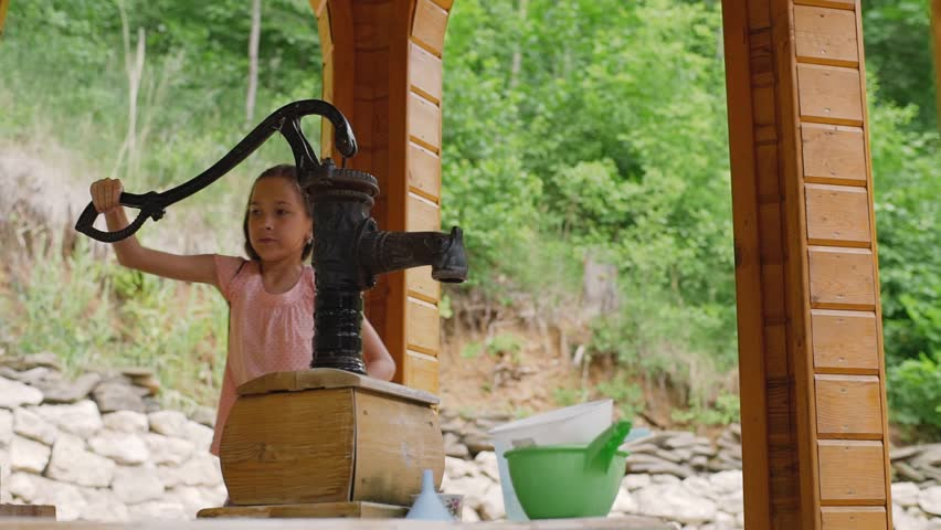 A young girl draws water from a water inlet column. The girl shakes the water.