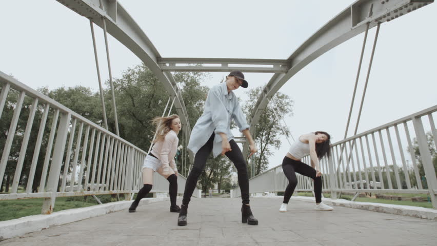 Pretty girls dancing and perform modern choreography hip-hop or vogue dance on the bridge in city park, posing, female artistic dancer contemporary freestyle in street style clothes | Shutterstock HD Video #1018919767