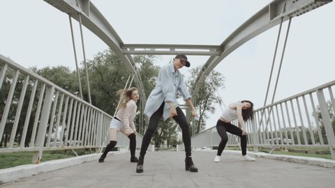 Pretty girls dancing and perform modern choreography hip-hop or vogue dance on the bridge in city park, posing, female artistic dancer contemporary freestyle in street style clothes