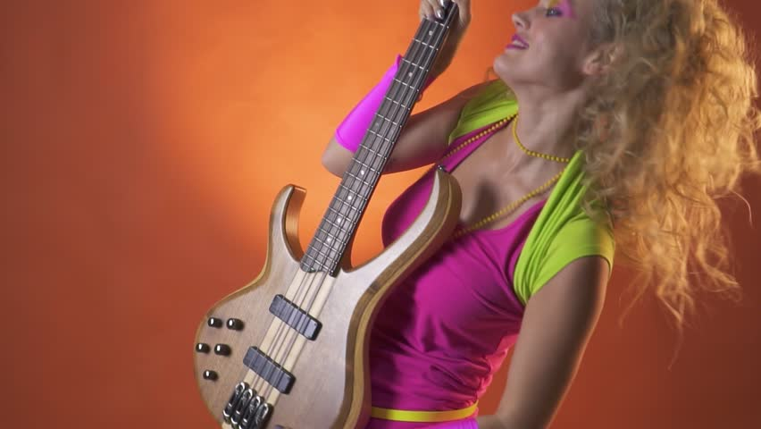 Playful woman in retro clothes, shakes her hair and dances with the guitar, slow motion | Shutterstock HD Video #1018946467