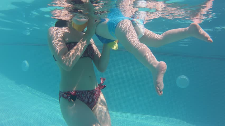 Under water. Happy mother and her child have fun in swimming pool.   Shutterstock HD Video #1018946527