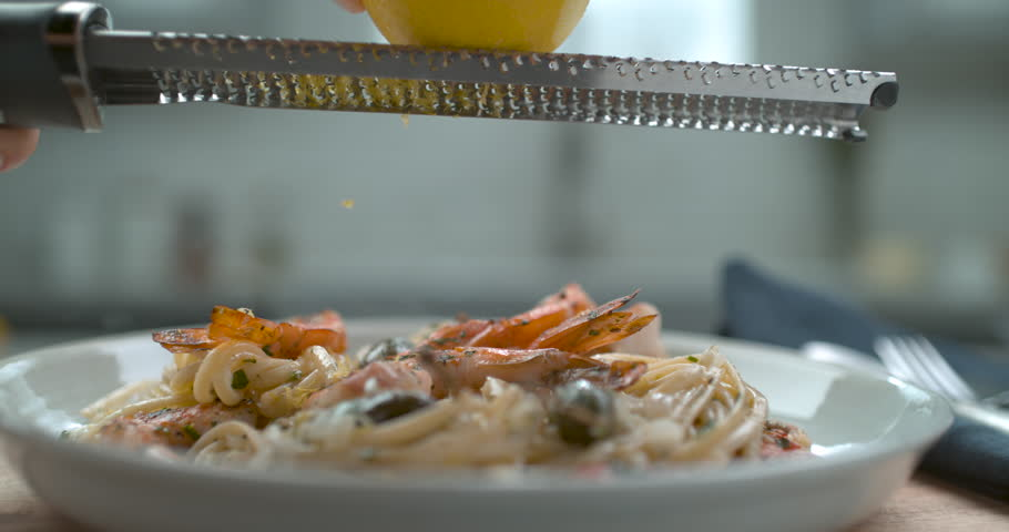 A chef's hand grates a lemon over a white plate of shrimp and olive linguini in interior restaurant kitchen with soft light. Closeup in 4k at 1000 fps on a Phantom Flex camera