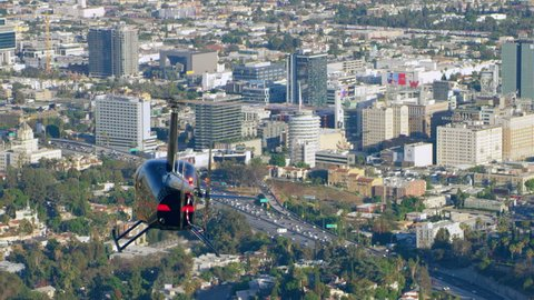 LA, California, USA, Circa 2018: Aerial view of helicopter flying over city with Hollywood sign in background during the day in Los Angeles, California. Shot on 4K RED camera.