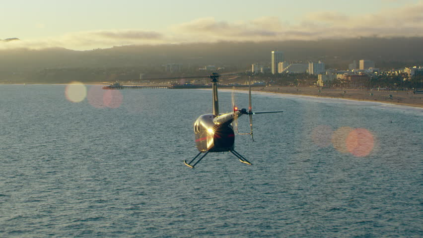 Aerial view of helicopter flying over ocean shoreline near pier during beautiful sunset in Los Angeles, California. Wide long shot on 4K RED camera. | Shutterstock HD Video #1019021947