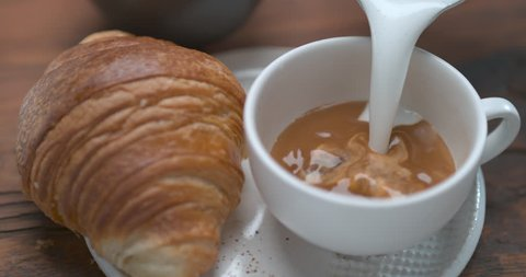 Mouth watering latte being poured in cup next to butter croissant ultra slow motion closeup with 4k Phantom Flex camera.