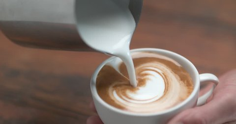 Barista making latte by pourring milk in white cup in ultra slow motion closeup with 4k Phantom Flex camera