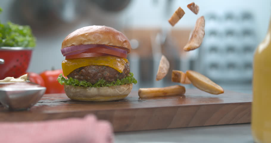 Hamburger heaven. The last food shot you will ever need. Mouthwatering crispy french fries falling super slow motion. Shot on phantom flex, 4k 1000fps. Get this shot before someone else gobbles it up.