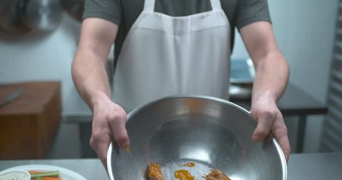 Male chef tossing chicken wings in 5 alarm hot sauce closeup in ultra slow motion with 4k Phantom Flex camera