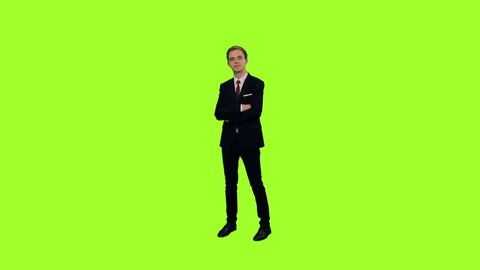 Young elegant man in suit looking at something on green chromakey background, Male standing with arms crossed on chest, Front view, 4k pre-keyed footege