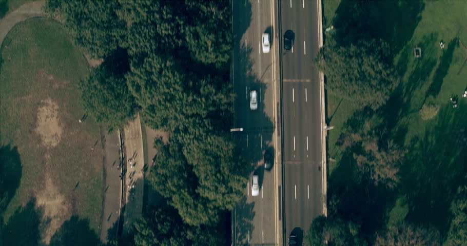 Aerial top down view of Manhattan cars driving near boardwalk in New York during the day under overcast blue sky. Wide shot on 4K RED camera.