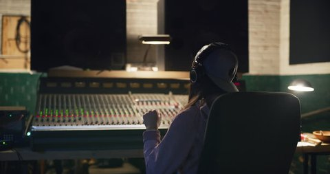 Sound engineer bobs her head to music she is working on at night in recording studio by professional mixing board. Medium shot on 4K RED camera.