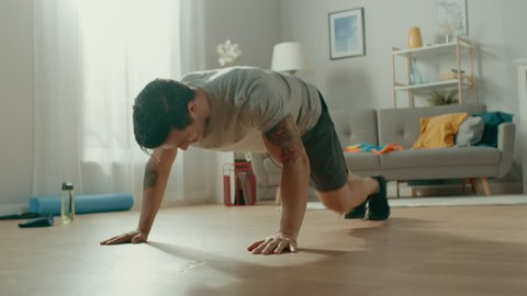 Strong Muscular Athletic Fit Man in T-shirt and Shorts is Doing Mountain Climber Exercises at Home in His Spacious and Bright Living Room with Minimalistic Interior.