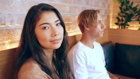 Asian girl sits with millennial friend waiting in restaurant in Australia during the day. Medium to closeup shot with 4K RED camera.