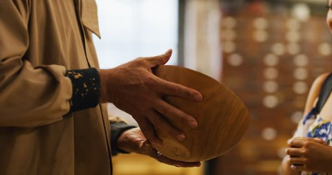 Young Asian woman uses credit card to buy wood bowl from older woodworking artisan man in workshop during the day. Medium to closeup on 4K RED camera.