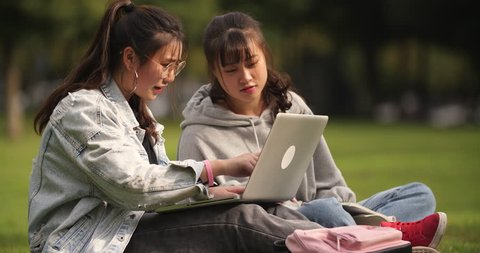 Two happy asian college girl sitting on the lawn using laptop and talking together in campus.