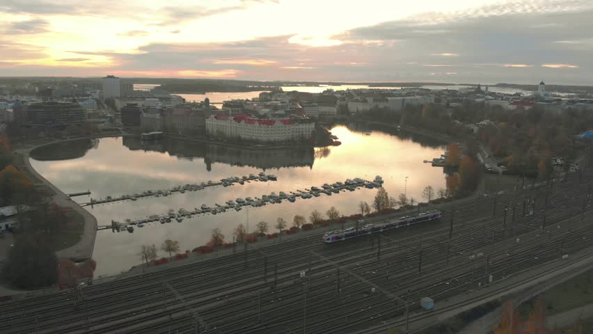 Cinematic aerial cityscape of train, railroad and sea bay during autumn sunrise. Water reflecting beautiful sky and clouds. Drone panning around moving train.  Helsinki Finland. | Shutterstock HD Video #1019219857