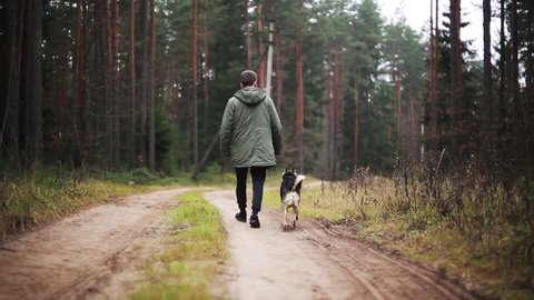 young man in a green jacket walks with a dog in the forest. Hike on nature with a pet.