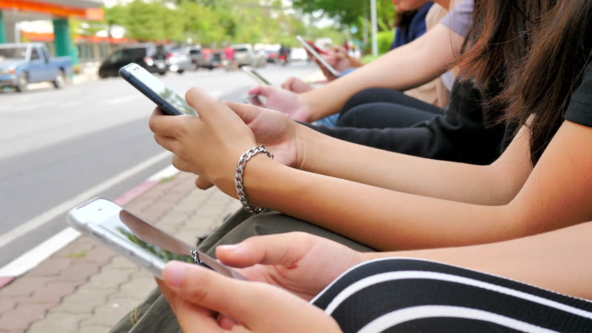 Group of friends using cellphones - Students sitting in a row and typing on the smartphones. | Shutterstock HD Video #1019318227