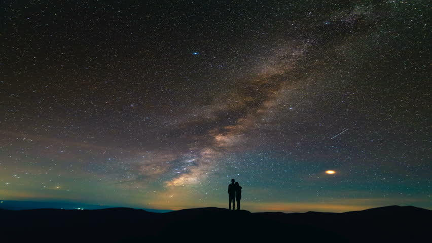 The couple standing on a background of a picturesque starry sky. time lapse #1019362327