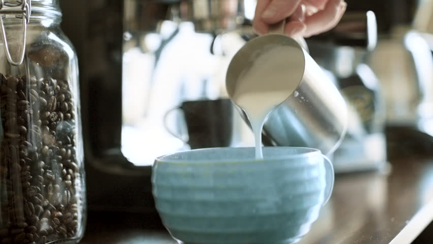 Barista Pouring Hot, Steamy, Frothy Milk into a Blue Mug Full of Fresh Espresso Coffee in Super Slow Motion   Shutterstock HD Video #1019382187
