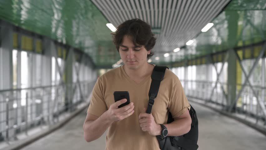 Attractive young caucasian man wearing beige t shirt and backpack is walking in tunnel, smiling and talking on smartphone. Tracking real time medium shot | Shutterstock HD Video #1019385547