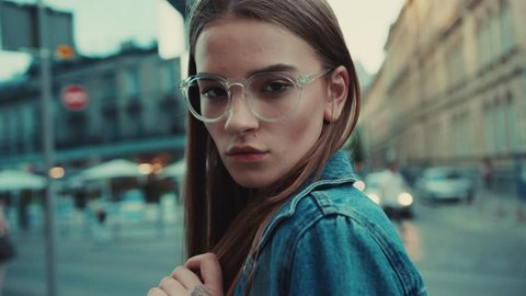 Portrait young woman with glasses look at camera poses in city center beautiful hair attractive smile girl lady jacket lifestyle summer close up face slow motion