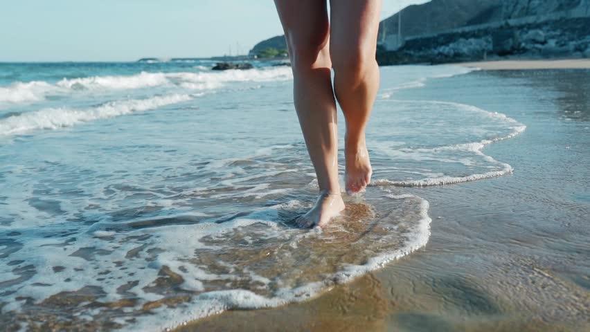 Female legs walking on water waves. Slim female legs move on water at sandy beach. | Shutterstock HD Video #1019415007