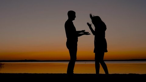 At sunset on the beach, silhouette of a man quarrels with a woman, she slaps him, beats with hands and swears, pushes him away, he begs her to forgive him, she go away. Slow motion.