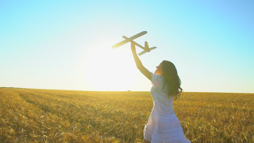 Cute cheerful girl in white dresses holding toy turbine in her hand running at sunset. Rear view. Wheat field. Day of sun and wind, happy woman in nature. Happiness, renewable wind energy, slow-motion | Shutterstock HD Video #1019458027