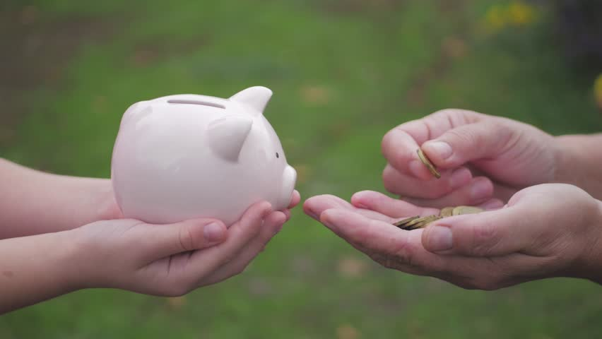 Mother and daughter child putting coins into piggy bank. Woman holds piggy bank while girl puts coins inside outdoor, lifestyle. Concept kid saving money for future.