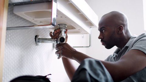 Young black male plumber sitting on the floor replacing the trap pipe under a bathroom sink, low angle